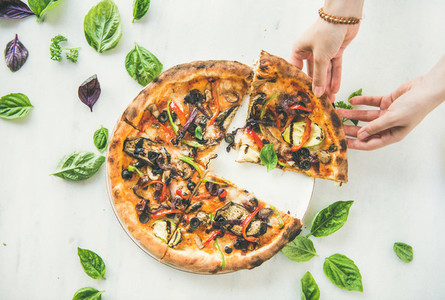 Womans hands taking Freshly baked vegetarian pizza over marble background