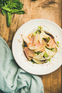 Fresh salad with smoked turkey ham and pear wooden background