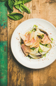 Fresh salad with smoked turkey ham and pear  rustic background