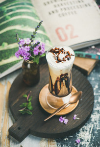 Iced mocha coffee with whipped cream in glass on board