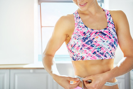 Smiling woman holding tape measure round her waistline