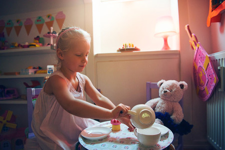 Girl serving tea for her toy bear