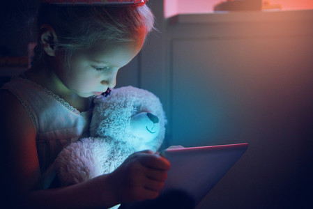 Cute girl hugging bear looking in tablet