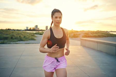 Muscular female athlete running in city park