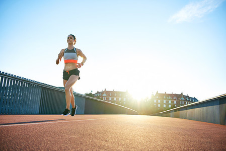 Low angle of sun behind woman running along bridge