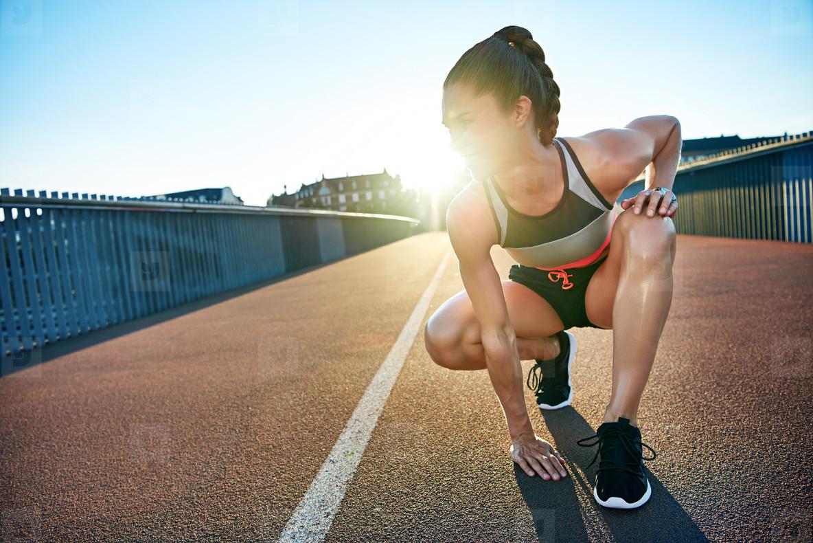 Sun highlights kneeling female jogger