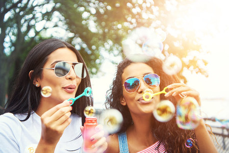 Female friends with sunglasses blow bubbles