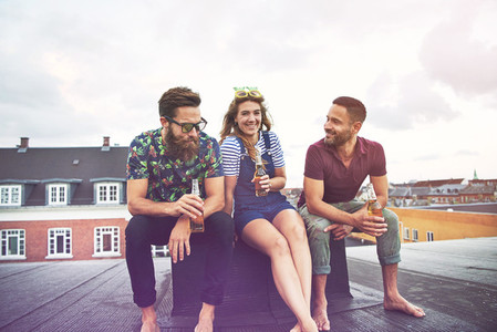 Two men and a woman drinking beer together on roof