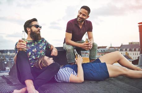 Woman in lap of bearded man near friend on roof