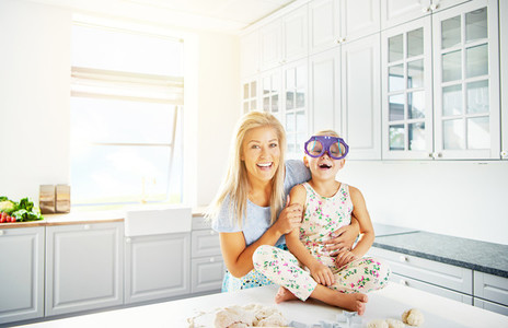 Woman holding happy child in silly glasses