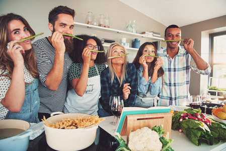 Silly adults sniffing asparagus stalks in kitchen