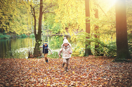 Two children running near the autumn pond