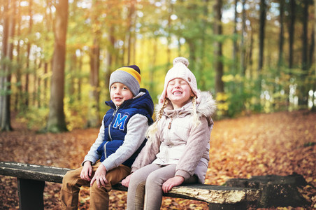 Two laughing kids sitting on a bench
