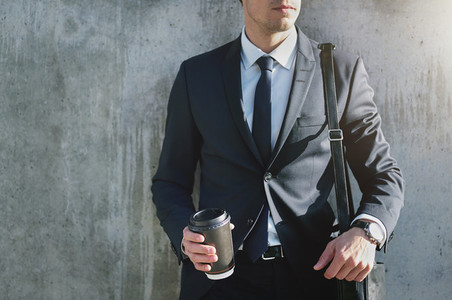 Successful worker with coffee cup in city