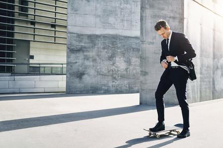 Businessman adjusting his necktie standing on skateboard