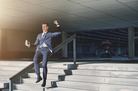 Happy businessman sliding down handrails with coffee