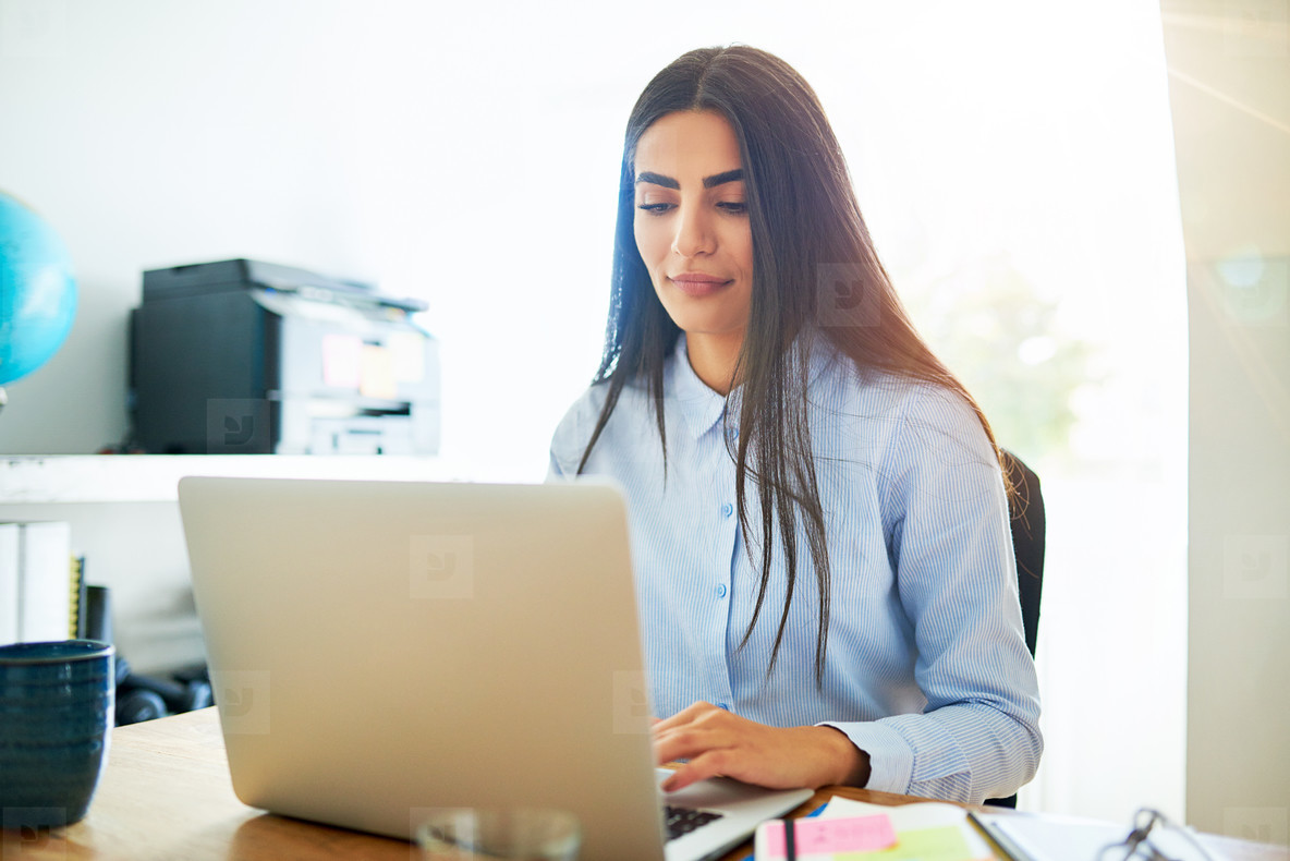 Calm young Indian woman working on laptop