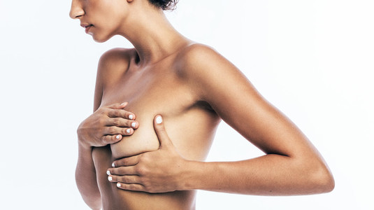 Woman her breast for cancer signs