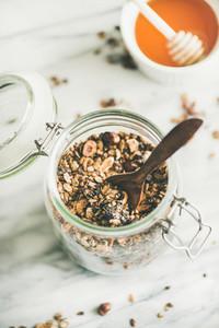 Buckwheat and chocolate granola with hazelnuts in glass jar