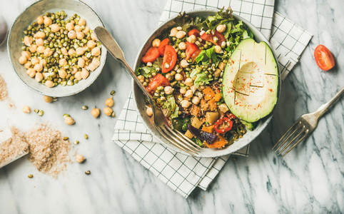 Flat lay of vegan dinner bowl with avocado  grains  beans  vegetables