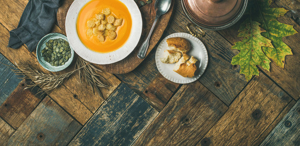 Fall pumpkin cream soup with croutons and seeds  wide composition