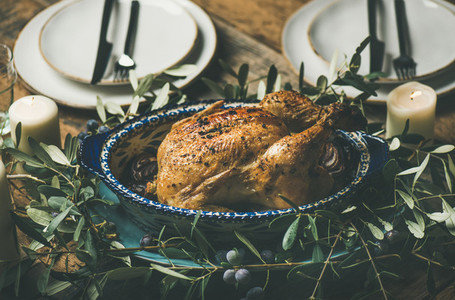 Whole roasted chicken decorated with olive tree branch  selective focus