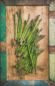 Raw uncooked green asparagus over rustic wooden tray background