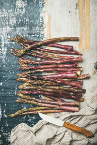 Fresh purple asparagus over rustic wooden background  vertical composition