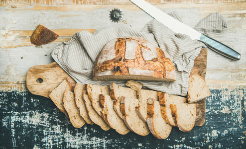 Flat lay of sourdough wheat bread cut in slices on table