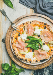 Freshly baked pizza with ham  artichokes  cheese and basil
