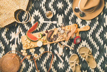 Picnic concept with sausage fruit cheese pate and straw accessories
