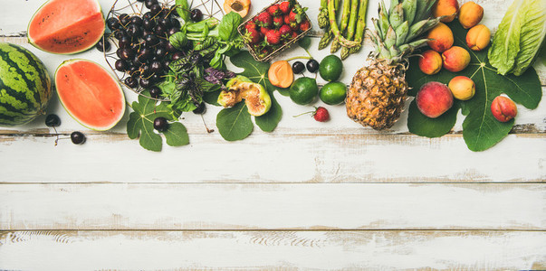 Flat lay of seasonal fruit  vegetables and greens over wooden background