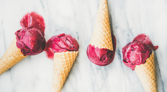 Melting natural raspberry sorbet ice cream scoops in sweet waffle cones