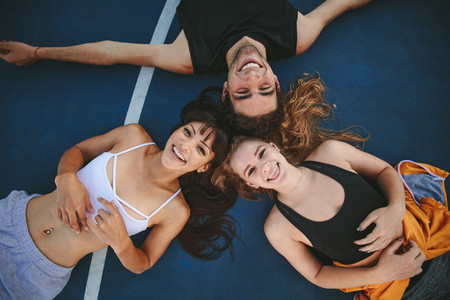 Friends lying down no basketball court