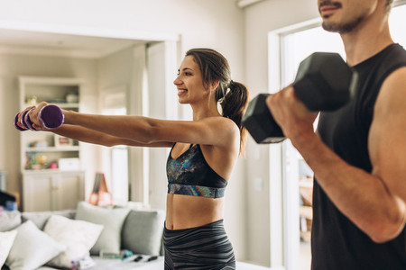 Couple doing weights workout at home