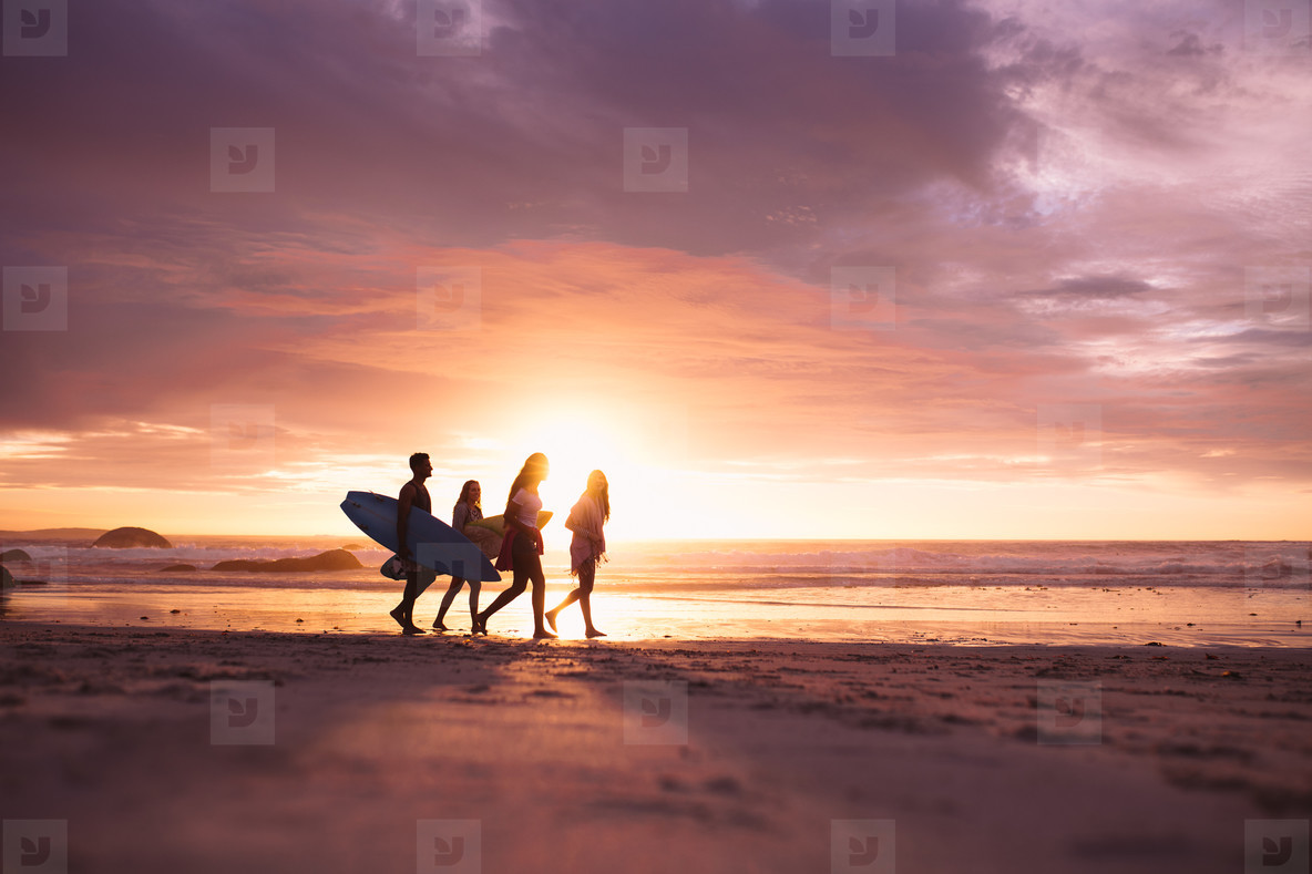 Silhouette of people walking on beach at sunset