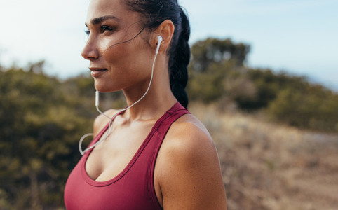 Athlete with earphones standing outdoors