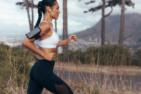 Woman athlete running on country road