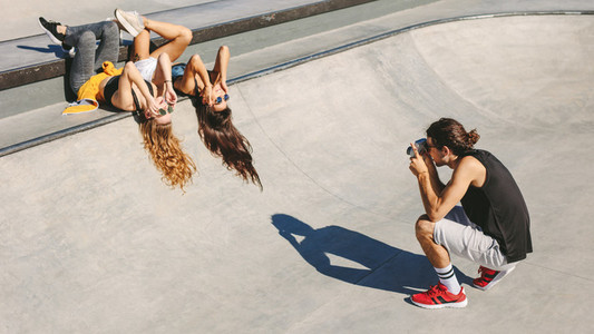 Photographer taking pictures of women at skate park