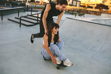 Couple enjoying skateboarding at skate park