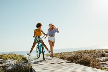 Two women having fun with a bicycle at beach