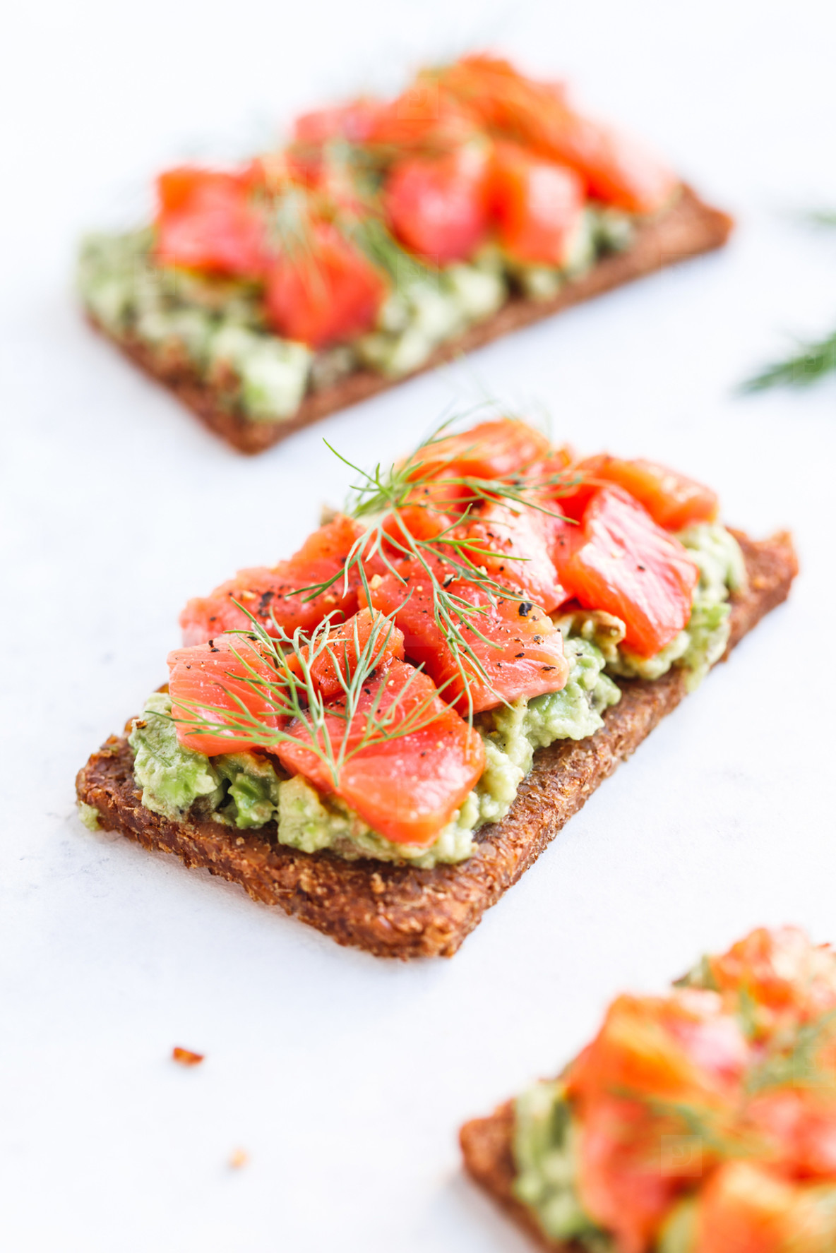 Close up view of three sandwiches with rye bread  avocado and smoked salmon on a white kitchen table