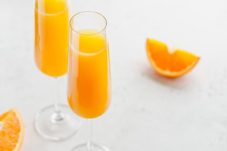 Brunch Mimosa classic cocktail is made from orange juice and sparkling wine or Champagne in flute glasses on a grey table