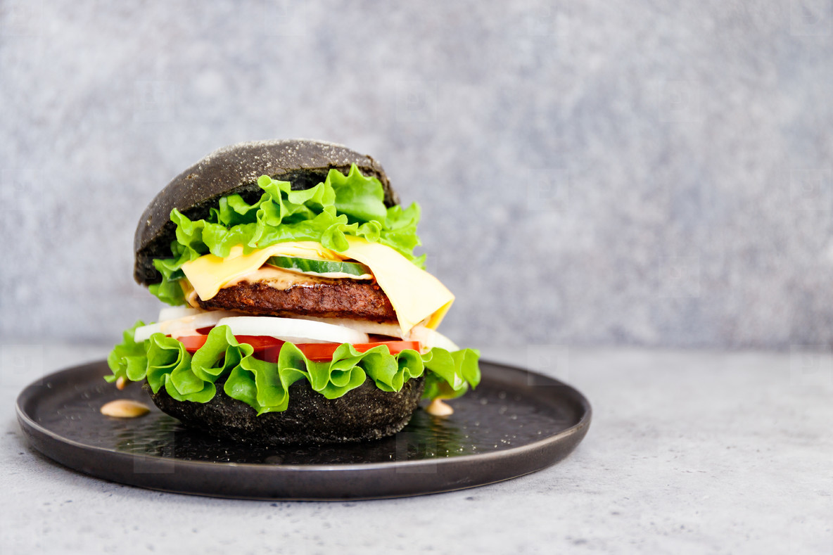Black burger with marble beef patty  cheese and fresh vegetables served on a black plat  Copy space
