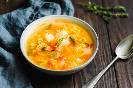 Spring vegetable soup with chicken stock for one person on wooden table   Rustic style  close up view