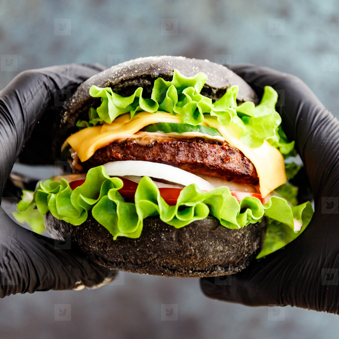 Hands in black gloves hold a big black burger with marble beef patty  cheese and fresh vegetables  Close up view