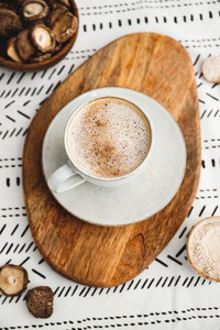 Mushroom latte with Shiitake powder and vegetarian blend milk on a wooden tray on a table  Healthy useful vegan drink