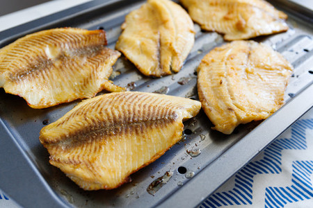 Close up of tilapia fillets on a broiling pan  Recipe for healthy home dinner or lunch