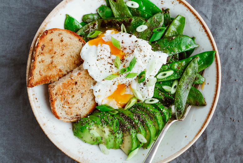 Top view of healthy breakfast or lunch  Fried snow peas  avocado  poached eggs are sprinkled chia seeds with toasts