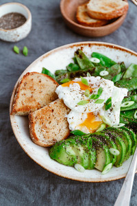 Healthy breakfast or lunch Fried snow peas avocado poached eggs are sprinkled chia seeds with toasts